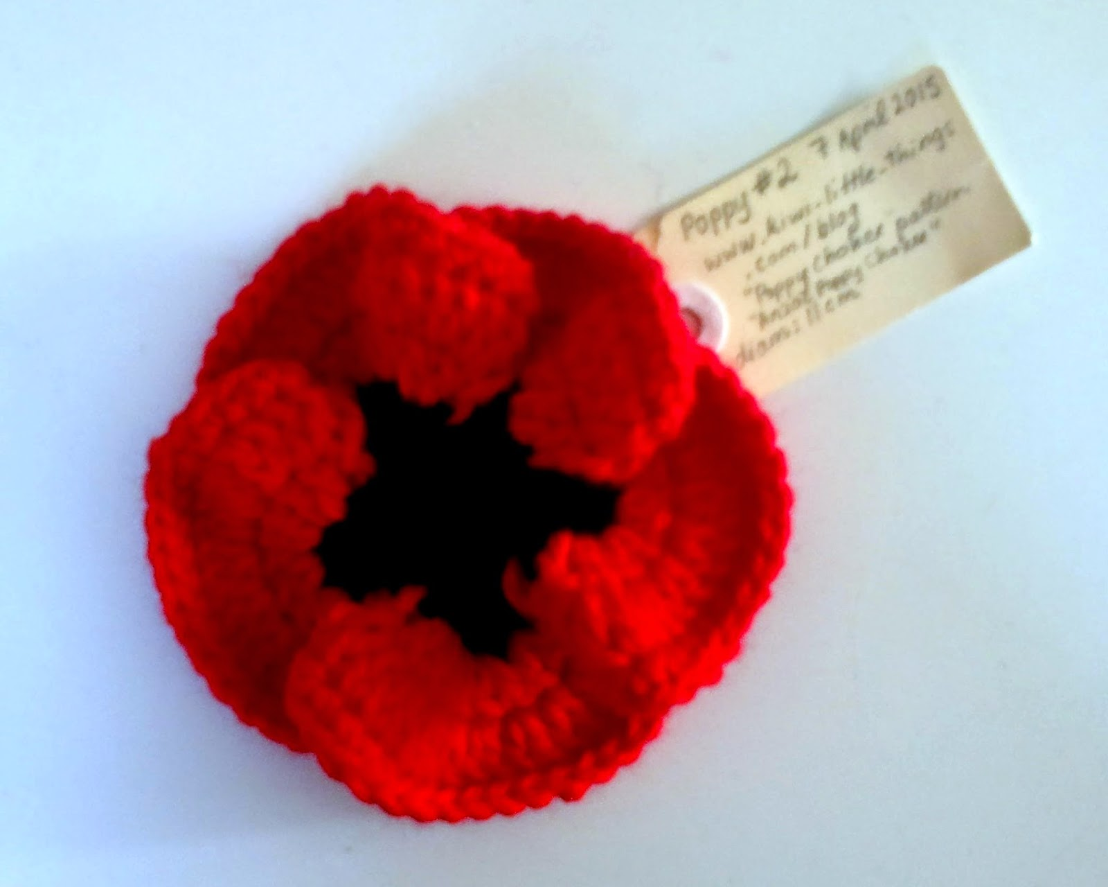 Red rosette style poppy with star-shaped black centre. The curved outer edges naturally overlap each other to resemble 5 petals.