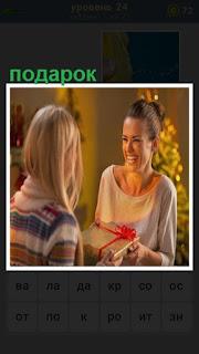 девушка дарит подарок подруге в коробке с ленточкой
