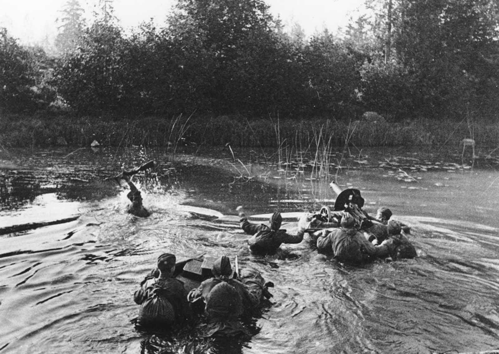 A Soviet machine gun crew crosses a river along the second Baltic front, in January of 1945. The soldier on the left is holding his rifle overhead while his comrades push a floating device with the a Maxim machine gun, followed by two men with several supply boxes.
