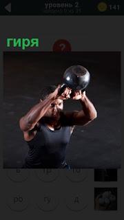Мужчина занимается спортом, поднимает гирю над головой