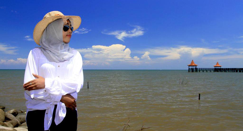cewek hijab manis pakai baju putih di pantai