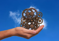 A hand holding a fanciful set of gears set against the sky