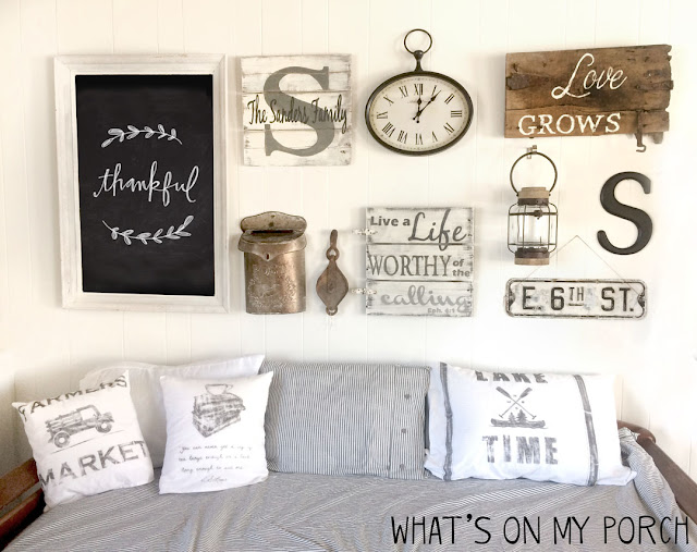 Farmhouse gallery wall with chalkboard, daybed, pillows, wood sign, clock