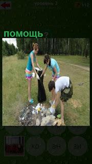 на поляне три девушки убирают мусор, тем самым оказывают помощь