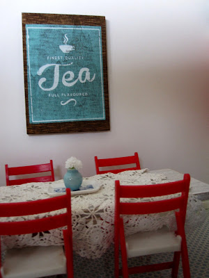 Modern one-twelfth scale miniature dining table with a cream lace cloth and red fold-up chairs set around it.