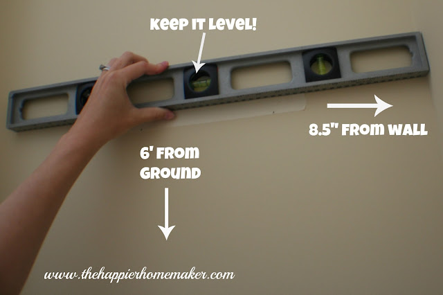 Someone holding masking tape with picture frame marks on it with a level on a wall to mark where the nails should go and be level