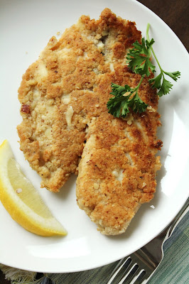 almond-crusted tilapia with lemon wedge and parsely