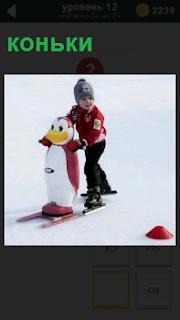 Мальчик на коньках двигает впереди большую игрушку пингвина, обучаясь катанию на льду
