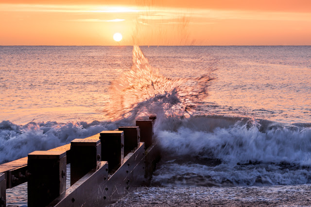 Sunrise wave splash on the beach at Swanage in Dorset