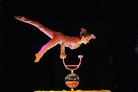Bir küre üzerinde tek eliyle dengede duran bayan akrobat