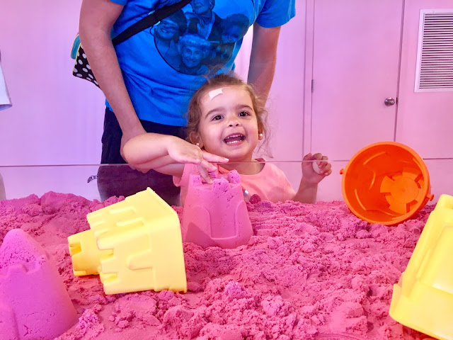 Toddler girl smiles and points to a pink kinetic sand castle that she built