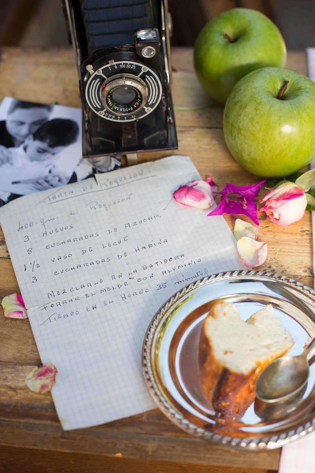 Tarta de requesón en plato de plata de con manzanas verdes con cámara de fotos antigua con flores rosas y púrpura