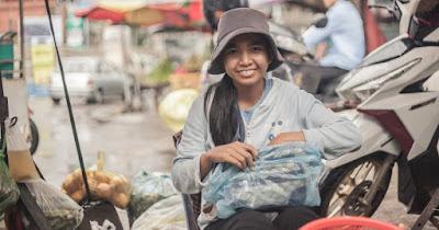 Una chica camboyana sonríe en un mercado.