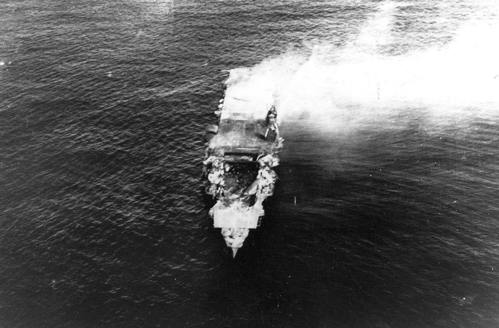 The heavily damaged, burning Japanese aircraft carrier Hiryu, photographed by a plane from the carrier Hosho shortly after sunrise on June 5, 1942. Hiryu sank a few hours later. Note collapsed flight deck over the forward hangar.
