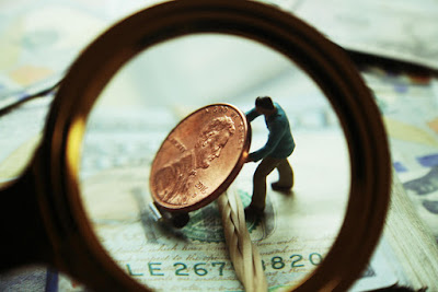 Magnifying glass directed towards a miniature man lifting a penny