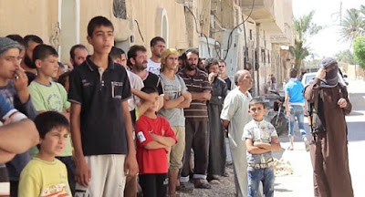 Children helped pelt two men with stones, as the Islamic State executed them for homosexuality. Homs, Syria, August 2015