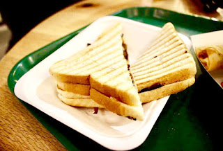 Two pieces of a white triangular sandwich with black grill marks scorched on it with a dark brown meat interior and white oozing interior to represent the cheese on a white square plate on a light background.