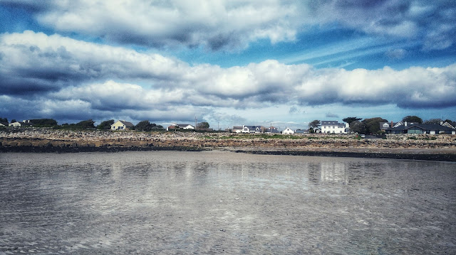 houses reflected in the water and the sand on the beach