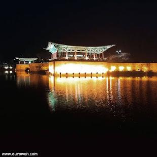 Construcción tradicional coreana sobre un lago iluminado con colores