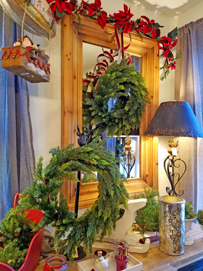 mirror a top console decorated for Christmas with wreath and red tones