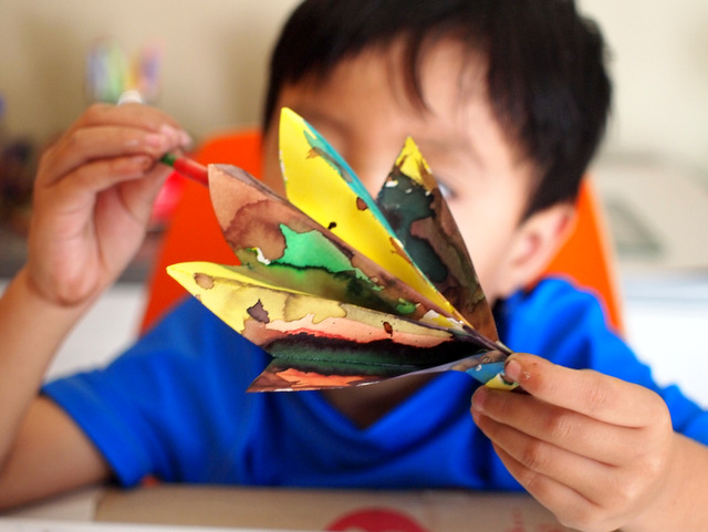 boy painting accordion folded fall paper leaf