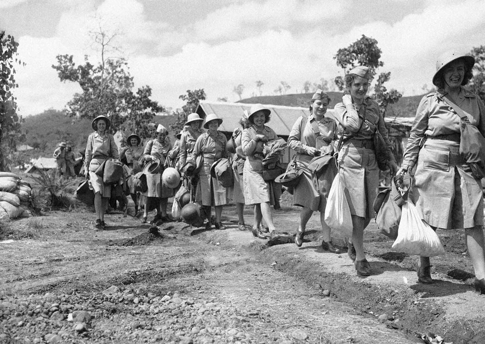 The first contingent of U.S. Army nurses to be sent to an Allied advanced base in New Guinea carry their equipment as they march single file to their quarter on November 12, 1942. The first four in line from right are: Edith Whittaker, Pawtucket, Rhode Island,; Ruth Baucher, Wooster, O.; Helen Lawson, Athens, Tennessee,; and Juanita Hamilton, of Hendersonville, North Carolina.