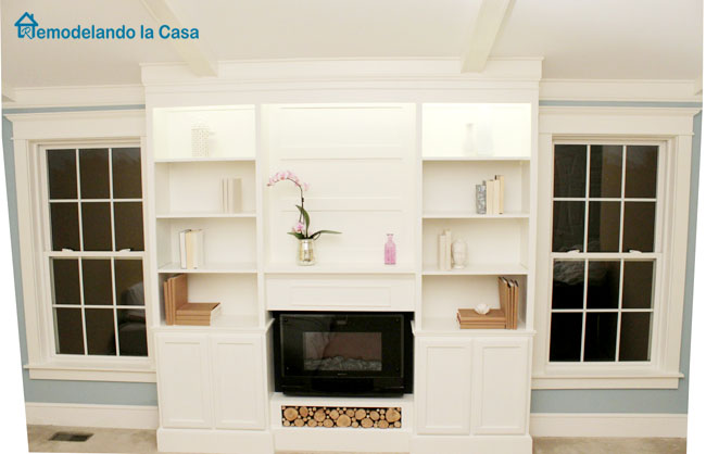 bookcase in between two trimmed windows