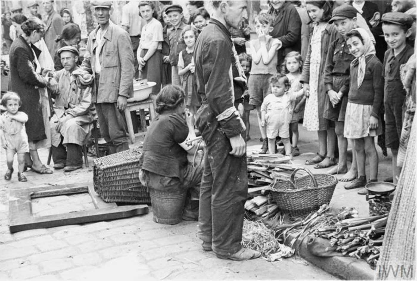 Jewish residents of the ghetto shopping in a vegetable street market.