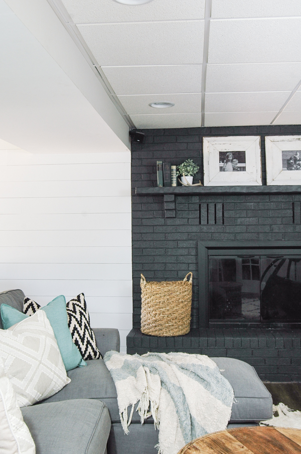 A gorgeous dark gray painted fireplace looks stunning paired with a bright white plank wall! - www.littlehouseoffour.com