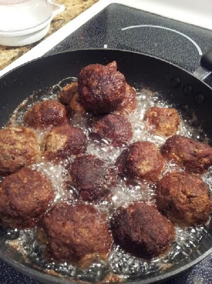 this is ground beef with herbs and spices added to make a round ball then fried in oil in a pan these are cooking in a heavy fry pan and the meatballs will be crispy on the outside and soft inside nicely browned using vegetable or canola oil
