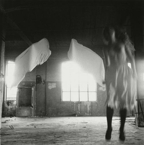 Coolstuff: una joven permanece volando en una habitación mientras que sus alas de angel reposan ante la luz.
