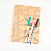 Adding gold leafing pen abstract designs to notebook covers