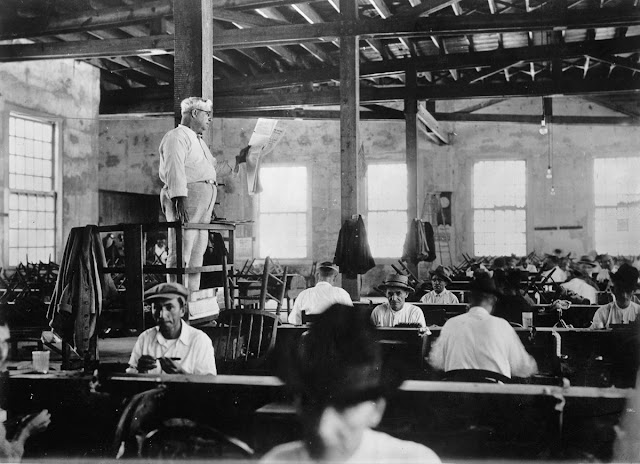 - A paid lector reads the newspaper to cigar rollers in Key West Florida. 1930s