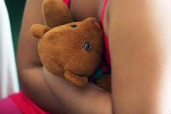 Fodo de um urso de pelucia sendo abraçado por uma criança, onde só aparece os braços dela