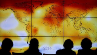 Participants are seen in silhouette as they look at a screen showing a world map with climate anomalies during the World Climate Change Conference 2015 (COP21) at Le Bourget, near Paris, France, December 8, 2015. (Credit: Reuters/Stephane Mahe/File Photo) Click to Enlarge.