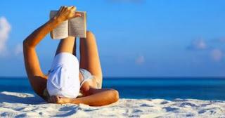 donna in costume che legge un libro distesa sulla spiaggia