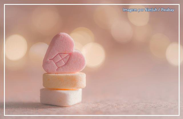 Imagem com fundo rosa de um bolinho em formato de coração, empilhado em cima de outros bolinhos