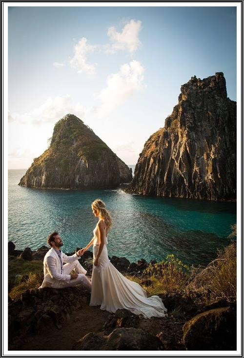 Paisagem marítima com elevações rochosas e um casal, a jovem em pé o jovem sentado olhando para ela e segurando sua mão.