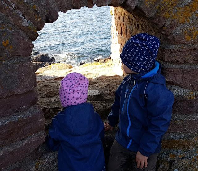 Bornholm mit Kindern im Herbst. Teil 3: 10 tolle Ausflugsziele für Familien auf Dänemarks Sonneninsel. Die Geschwister gucken auf Frederiksö durch eine Schießscharte aufs Meer.