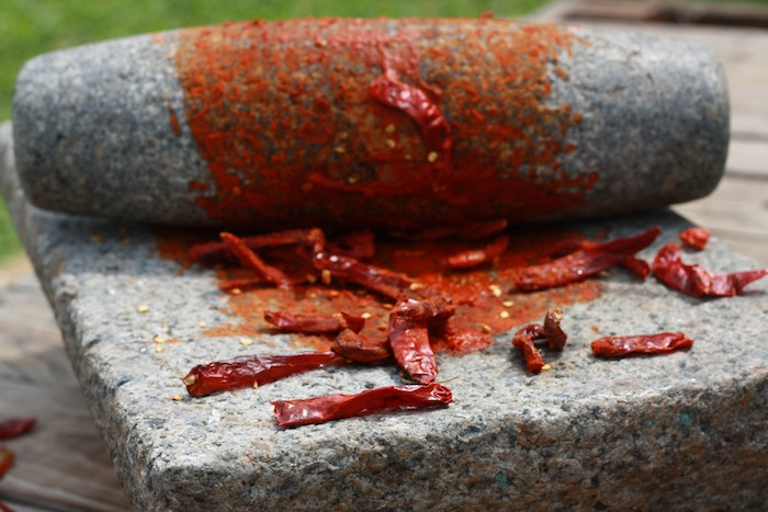 ground red chilies with traditional mortar and pestle roller