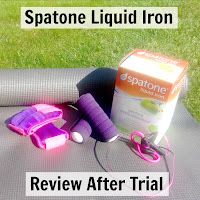 Spatone Liquid Iron packaging amongst hand weights on a yoga mat.