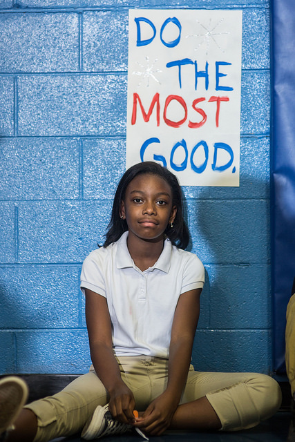 image of a Black girl sitting on the floor in what looks like a school hallway; behind her on the wall is a sign in red and blue lettering on a white background reading: 'Do the Most Good'