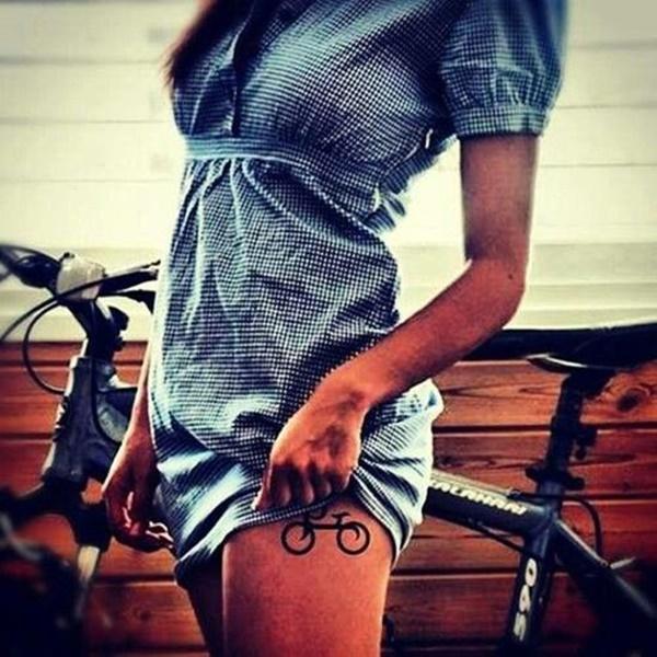 imagen del tatuaje en la pierna de una modelo, lleva una bicicleta pequeña
