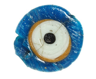 Circular glass eye - blue round the outside edge with black dot for pupil in centre