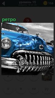 Передняя часть ретро автомобиля вся блестит синего цвета