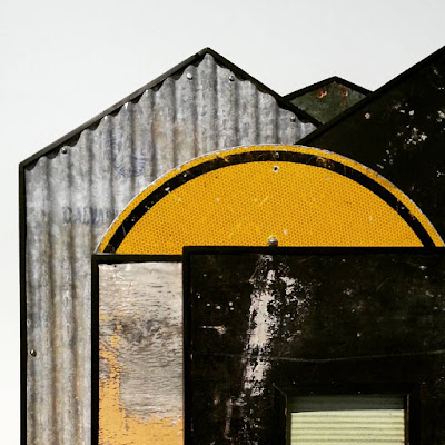 Detail of an assemblage art piece by Alex Asch, made up of various pieces of distressed corrugated iron and board, and part of a road sign.