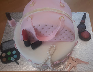 Pink cake decorated and shaped like a purse with small pieces decorated as eye makeup compact, lipstick, rouge and a brush, keys, nail polish bottle, and a string of pearls