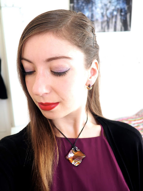 Evil Queen Disneybound villain outfit jewellery details of purple and gold stud earrings and chunky square pendant necklace, with purple eyeshadow and red lipstick