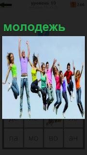 В воздух подпрыгивают молодежь, одета в разноцветные одежды и в радостном настроении