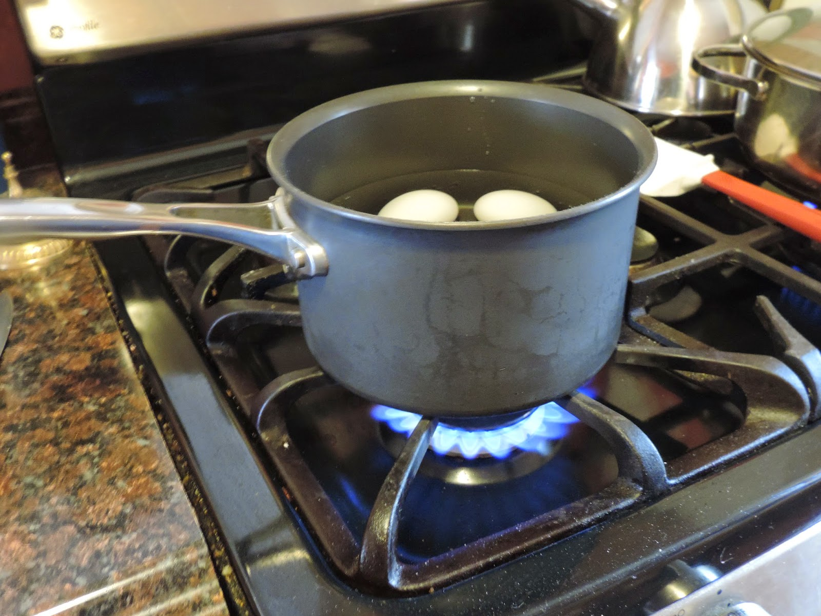 The pot of eggs and water being placed over medium/high heat on the stove.